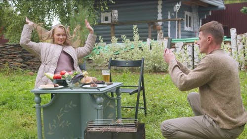 A Woman Poses for Her Man in the Courtyard of the Dacha at a Table with Food, He Takes It on a
