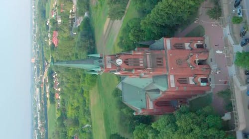 Church in Small City Among Pastures. Drone Footage. Red Church Is Roman Catholic Church.