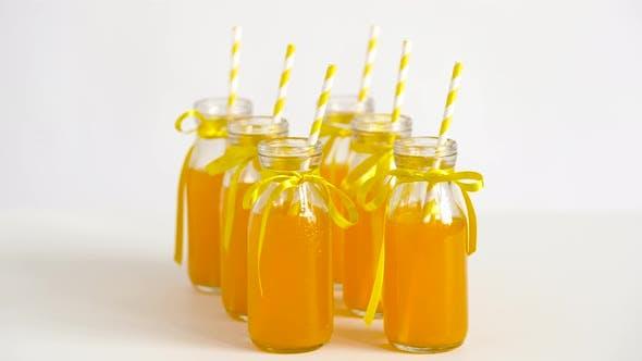 Saft oder Limonade in Glasflaschen mit Strohhalmen