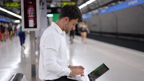 Businessman Using Laptop on Station