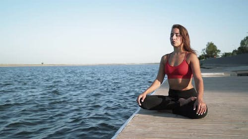 Athletic Woman Sitting in lotus position and Doing Yoga on Lake Background. Girl Exercising Outdoors