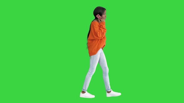 Emotional African American Woman in Bright Jumper Talking on the Phone While Walking on a Green