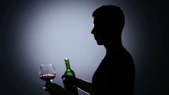 Thumbnail for Man Pours Wine Into a Glass and Then Drink It. Back Light