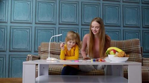 Lovely Mother Babysitter Teacher Helping Kid Daughter with Homework Learning Writing at Home