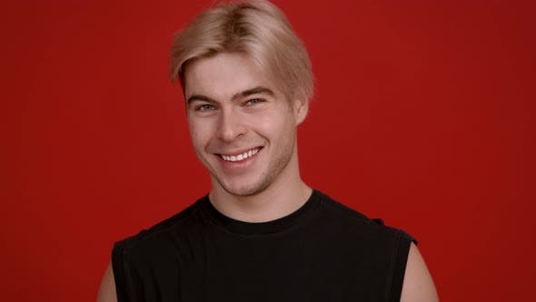 Close Up Studio Portrait of Happy Blonde Guy Laughing at Camera Red Background Slow Motion
