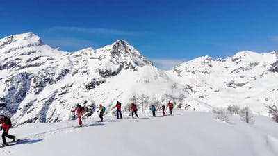 Group of ski touring on skin uphill in a line. Ski touring in big mountains