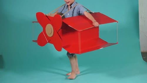 Little Caucasian Boy Flying on Red Cardboard Airplane, Happy Boy in Casual Clothes Wearing Pilot