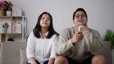 Young couple disputing about remote in living room