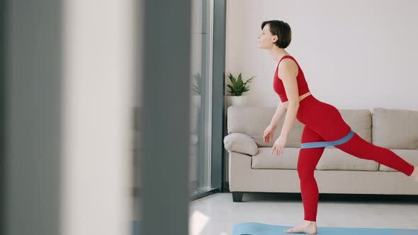 The Woman Is Doing Butt Exercise with a Fitness Band