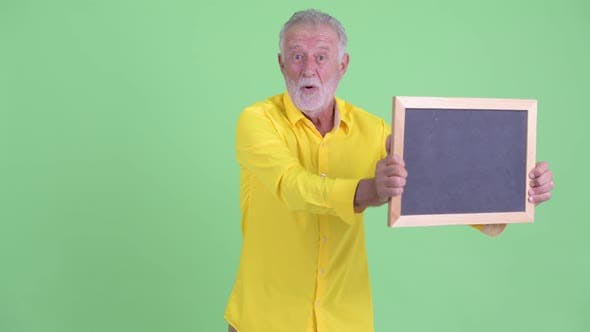 Thumbnail for Happy Senior Bearded Businessman Holding Blackboard and Looking Surprised