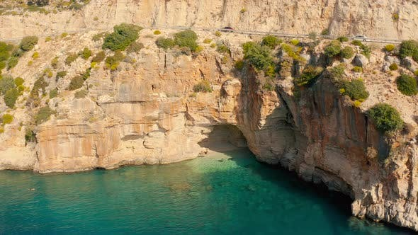 Thumbnail for A Couple of Travelers Swims in a Hidden Cove with a Cave in Mountain on the Road From Demre