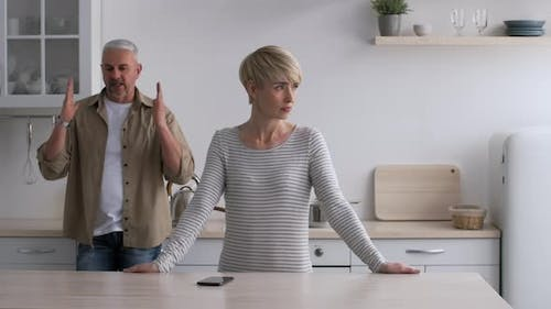 Unhappy MiddleAged Couple Having Quarrel Standing In Kitchen At Home