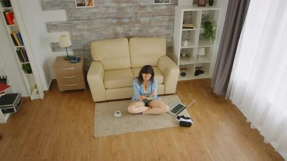 Frau liest auf dem Boden