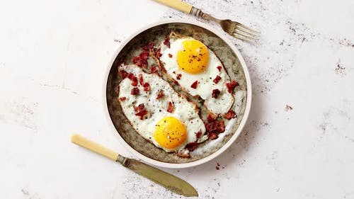 Two Fresh Fried Eggs with Crunchy Crisp Bacon Served on Rustic Plate