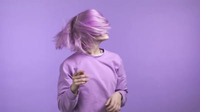 Attractive Woman with Purple Hairstyle Dancing on Purple Studio Background Her Hair Fluttering From