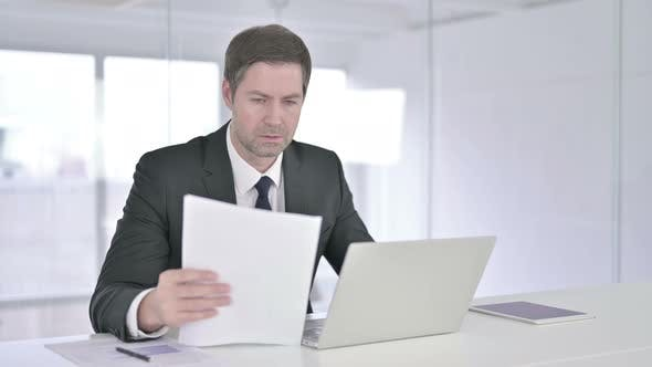 Thumbnail for Middle Aged Businessman Reading Documents and Working on Laptop