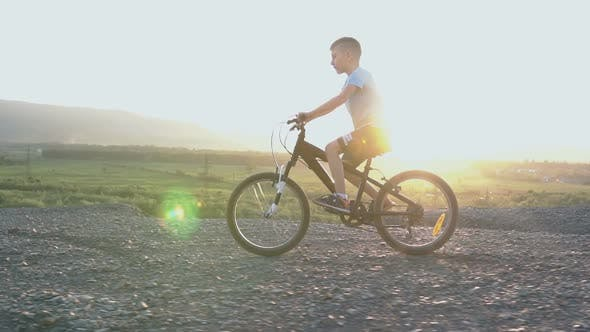 Cover Image for Little Kid Riding Bike in Summer Top of Mountain at Beautiful Sunset Sky Background