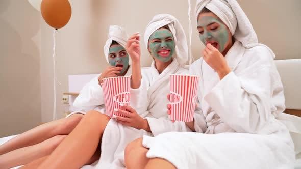 Thumbnail for Girls Eating Popcorn in Bed, Having Fun.