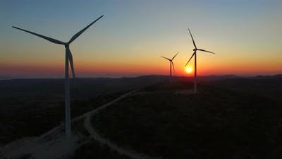 Aerial view of sustainable windmills at beautiful colorful sunset