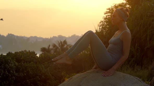 Thumbnail for Girl Stands in Navasana on Large Rock at Sunrise Slow Motion