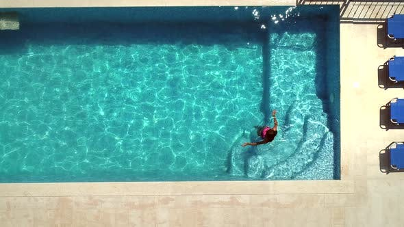 Thumbnail for Aerial view of young woman walking and swimming in pool.