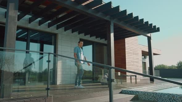 Thumbnail for Schöner Mann Stretching auf Terrasse. Geniessen Sie Erfolgs-Lifestyle