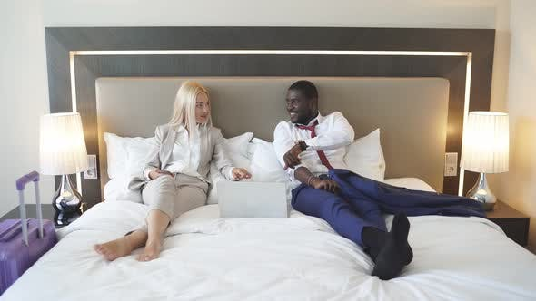 Beautiful Diverse Couple Lie on Bed with Laptop.