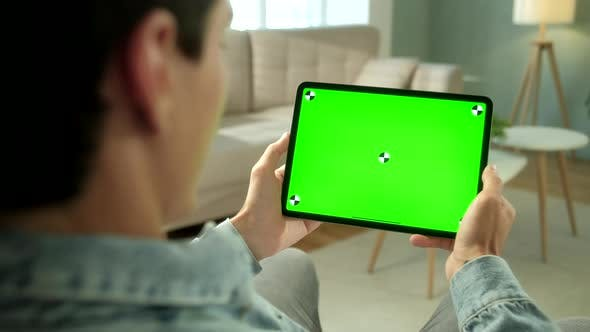 Thumbnail for View From the Shoulder of Man Using Hand Gestures on Green Mock-up Screen Digital Tablet Computer in