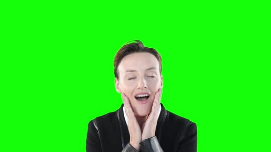 Surprised Caucasian woman smiling at camera on green background