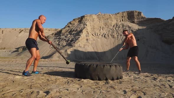 Thumbnail for Two Male Athletes Training Together Hit the Wheel with a Hammer at Sunset in the Mountains