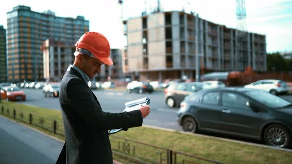 Thumbnail for Construction Worker. Architect Look at Paper Plan of Building