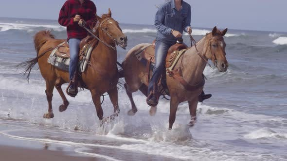 Women riding horses at beach in slow motion