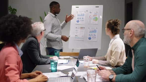 Young Black Man Giving Business Presentation to Team at Office Meeting