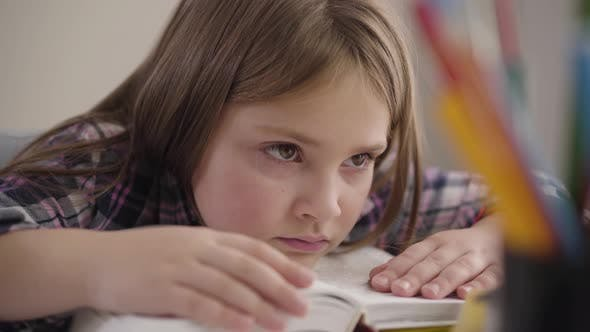 Thumbnail for Close-up of Pretty Caucasian Brunette Girl with Brown Eyes Holding Head on Book. Tired Schoolgirl