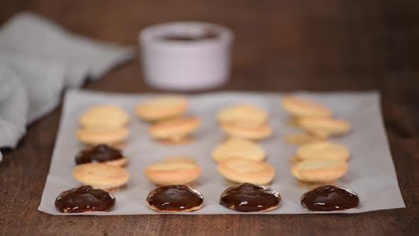 Koch schmückt Kekse mit geschmolzener Schokolade
