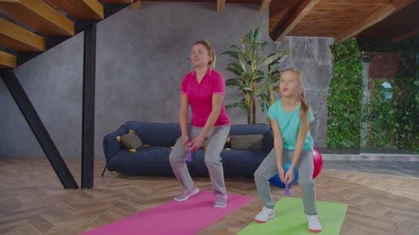 Sportlich Fit Mama und Mädchen Doing Dumbbell Sumo Squat