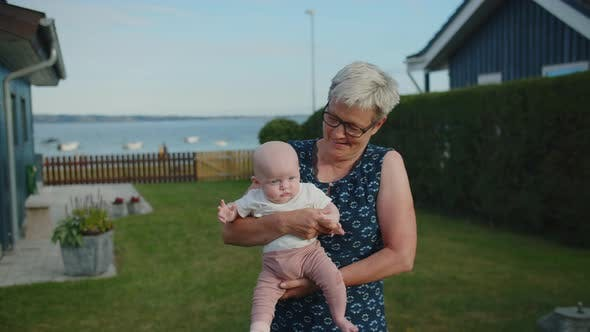 Thumbnail for Grandmother Holding Baby Girl In Garden