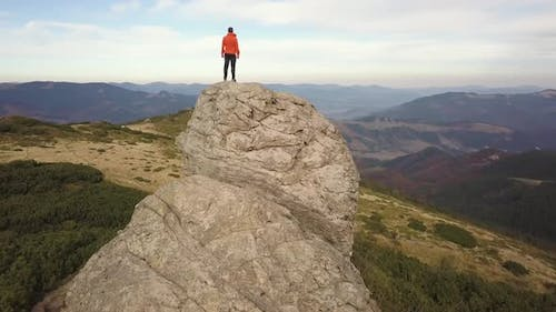 Aerial view of a hiker man climbing big rock in mountains.