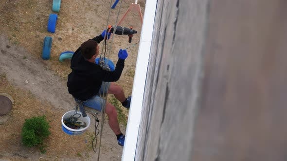 Industrial Climber Suspended on Ropes Insulates Facade with Styrofoam Near Wall