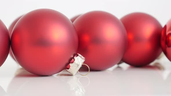 Christmas ornaments in red matte color on white background slow tilt 4K video