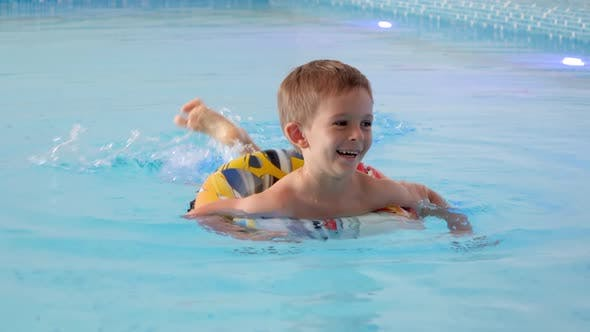 Happy Smiling Little Boy Swimming in Indoor Swimming Pool