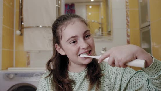 Thumbnail for Girl Brushing Her Teeth with an Electric Toothbrush. Fron View