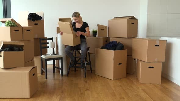 Thumbnail for A Moving Woman Sits on a Chair and Puts Things Into a Cardboard Box in an Empty Apartment