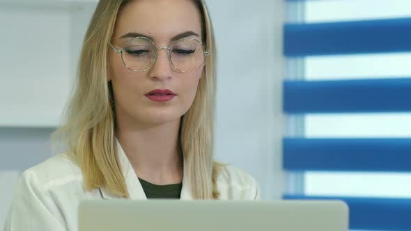 Thumbnail for Concentrated Female Doctor in Glasses Working on Laptop at Reception Desk