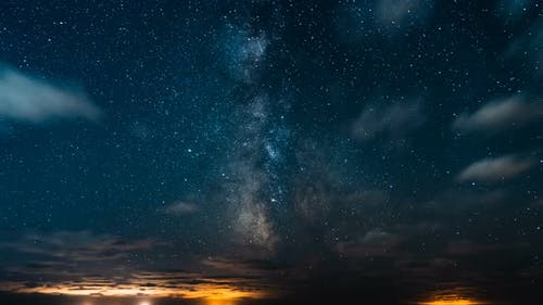 Milky Way With Stars And Galaxies In The Night Sky With Moving Clouds