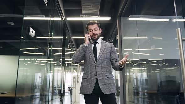 Thumbnail for Businessman which Walking Through the Modern Company Hall and Talking on Smartphone