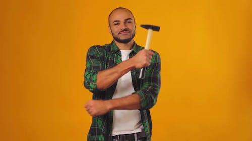 Afroamerikaner Mann im grünen Hemd stehend mit Hammer in den Händen vor gelbem Hintergrund