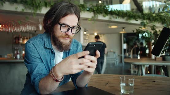 Thumbnail for Male Browsing Smartphone in Cafe