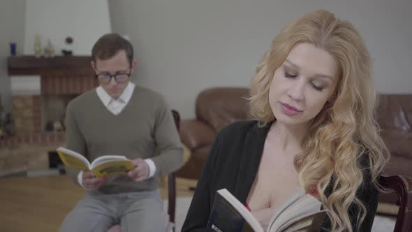 Thumbnail for Beautiful Blond Woman Reading the Book in the Foreground While Modestly Dressed Man Studying