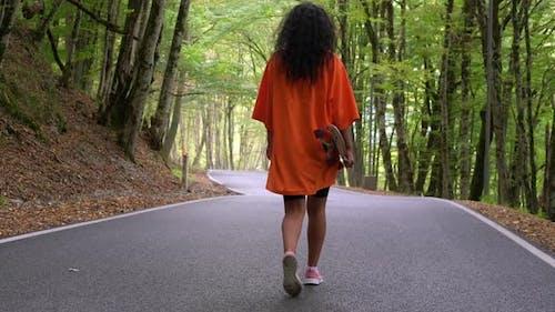 Girl Skateboarder Walking Along the Parkway